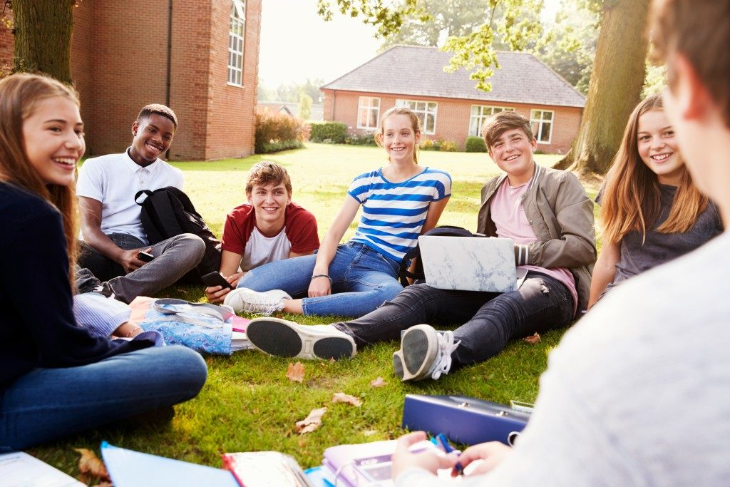 Teenage students sitting outdoors
