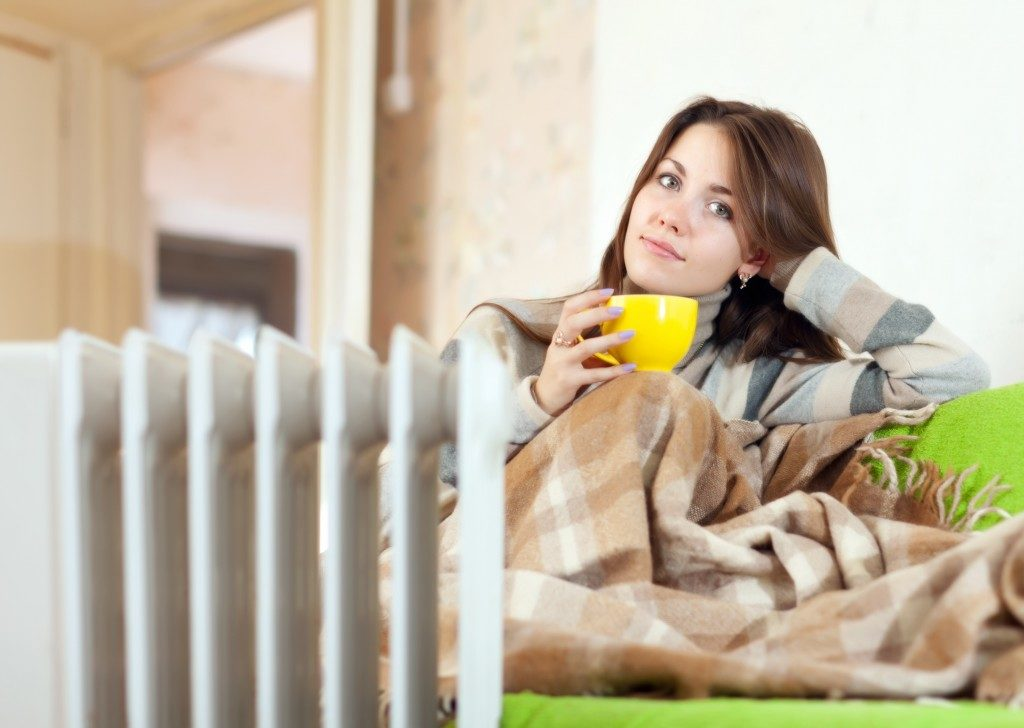 woman cozying in her home with heater keeping her warm