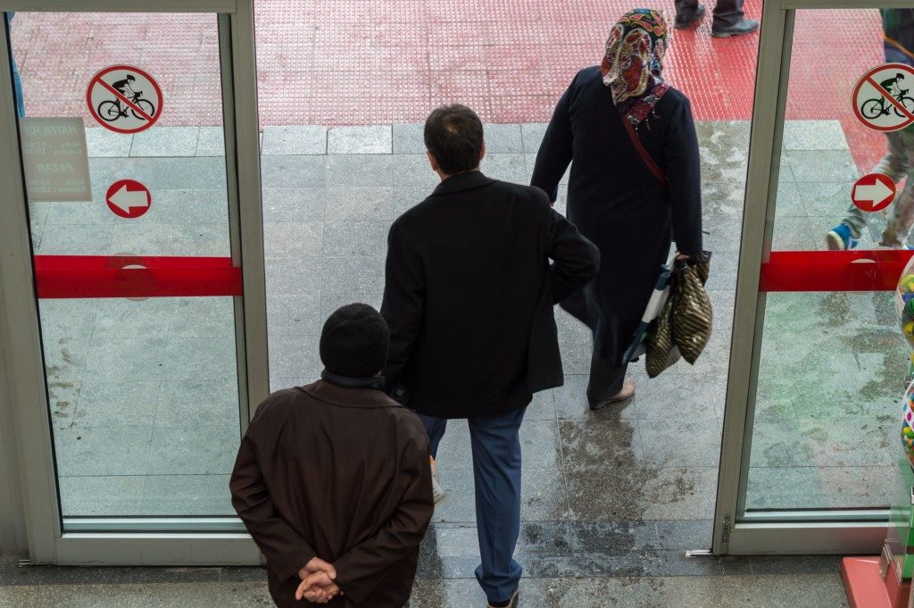 people exiting automatic sliding door
