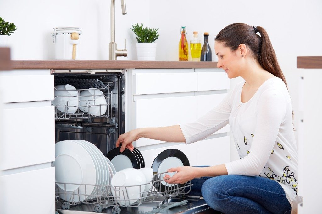Woman getting plates from the dishwasher