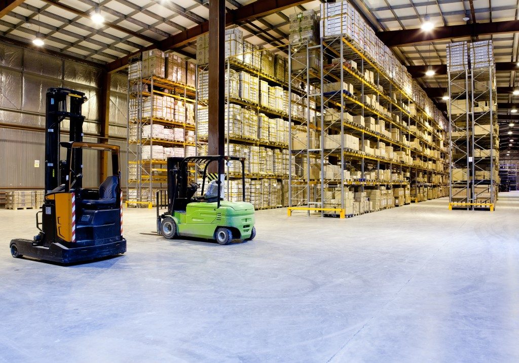 Warehouse with orange and green forklifts