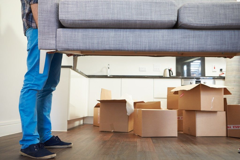 man carrying sofa in redesigned garage area