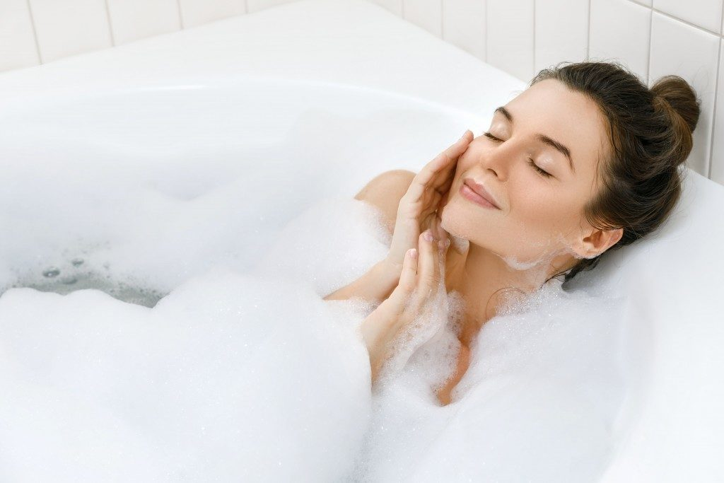 woman enjoying relaxing bath at home