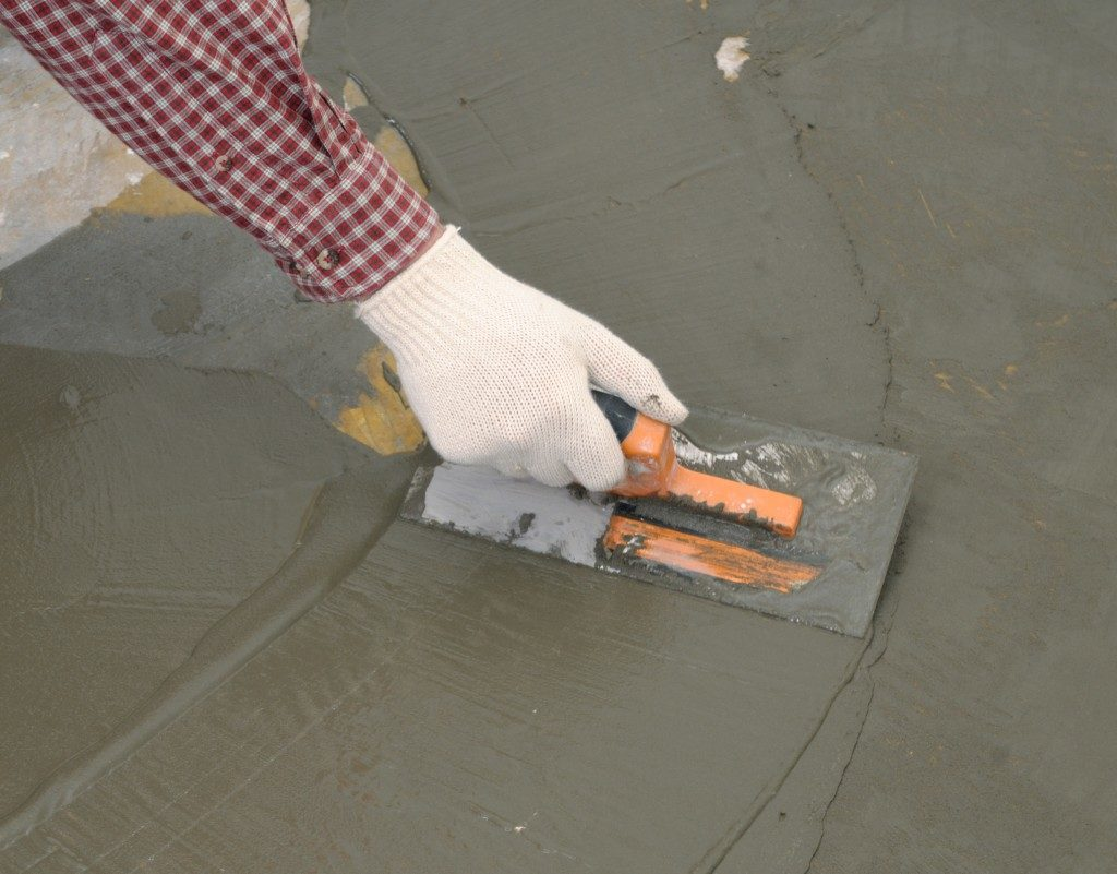 Construction worker spreading wet cement