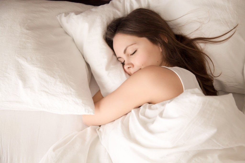 Woman sleeping while higging her pillow