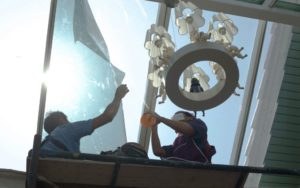 workers putting window film on conservatory window