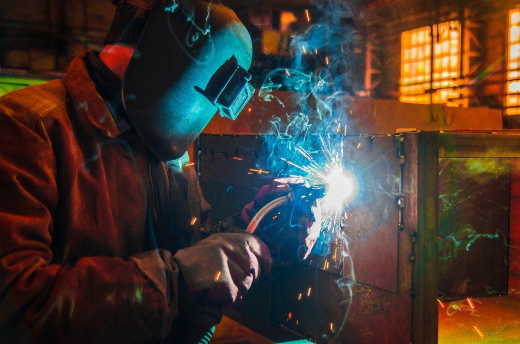 Man-welding-metal-while-wearing-safety-helmet