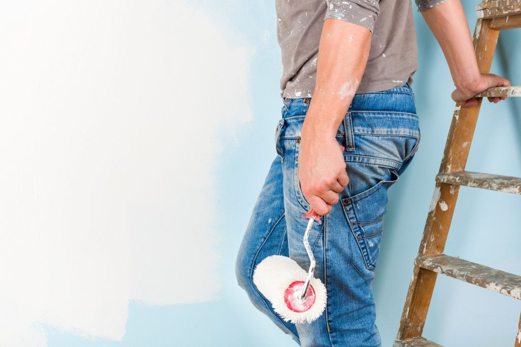 Man painting the wall white