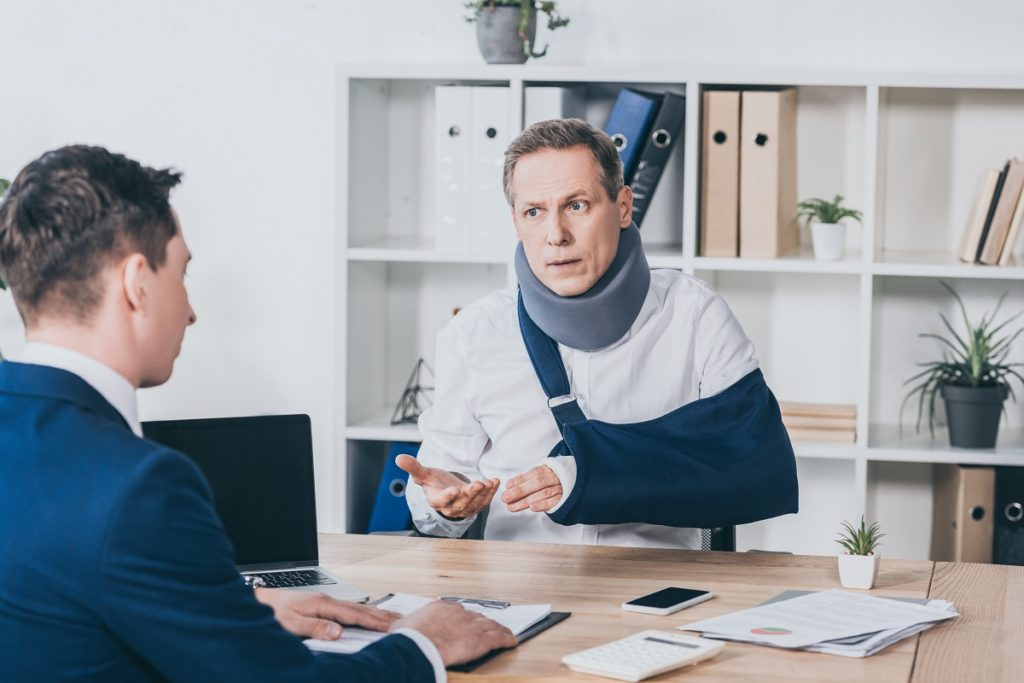 Man with injuries talking to his employer