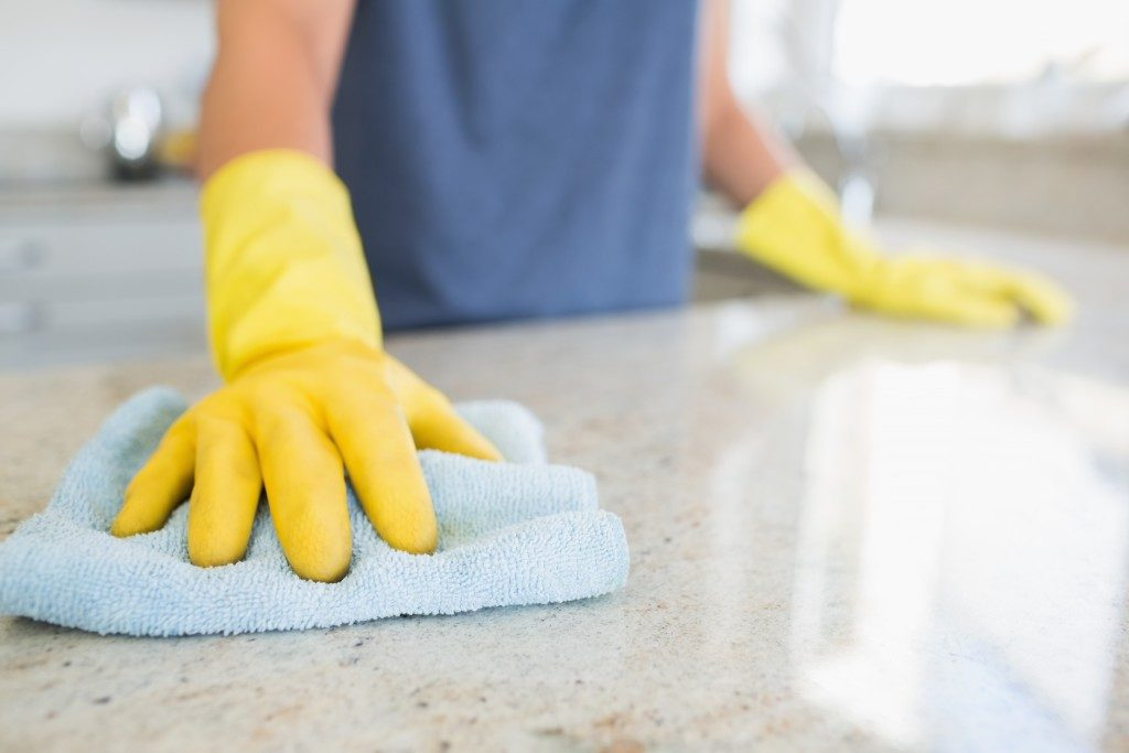 woman cleaning and wiping kitchen counter