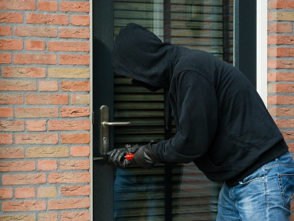 Burglar opening a locked door of a house