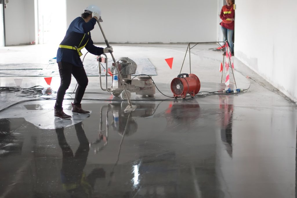 construction applying epoxy on the floor