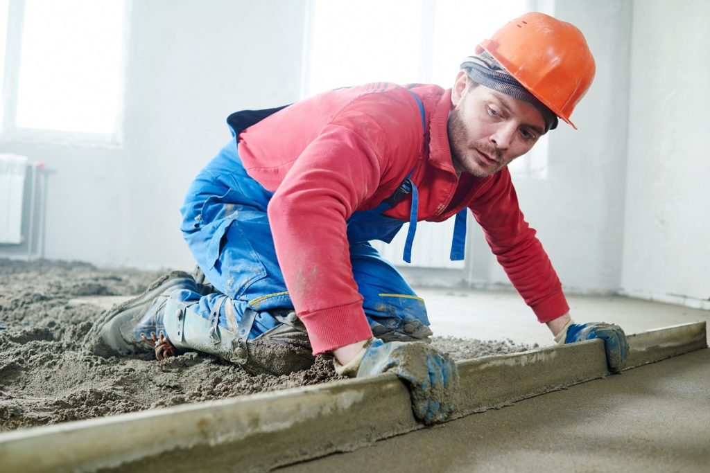 construction worker putting cement on the floor