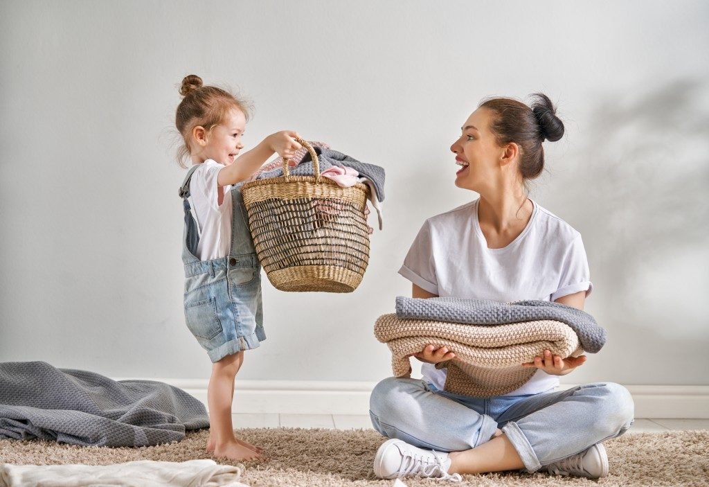mother folding laundry with child