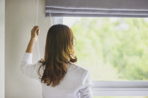 Female putting down blinds